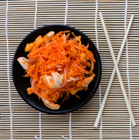 korean salad: Korean salad of grated carrots with red fish and onions marinated and chopsticks on a wooden mat, Close-up, top view
