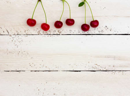 duckboards: red ripe cherries on top of the white horizontal boards. Copy space. Free space for text Stock Photo