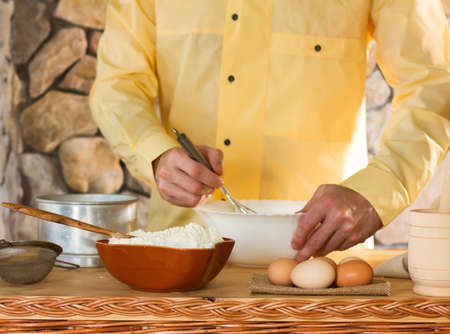 yellow flour: in the foreground is a bowl of flour, eggs, a sieve and a mortar in the background a male chef in a yellow garment whisk the whisk the batter. concept country kitchen, selective focus Stock Photo