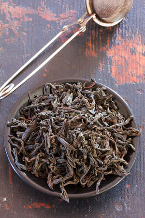 unpressed: steel strainer dried black tea leaves in round black saucer on old wooden table, top view