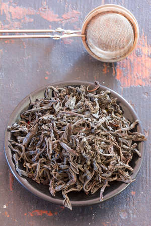 unpressed: steel strainer dried black tea leaves in a round black saucer on old wooden table close-up, top view