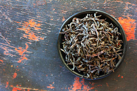 unpressed: Dried black tea leaves in round black saucer on old wooden background. Copy space. Free space for text, Close-up, top view