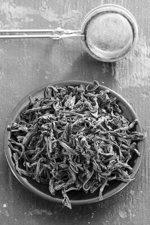 unpressed: steel strainer dried black tea leaves in a round black saucer on old wooden table close-up, top view. black and white photo