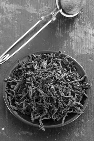 unpressed: steel strainer dried black tea leaves in round black saucer on old wooden table, top view. black and white photo