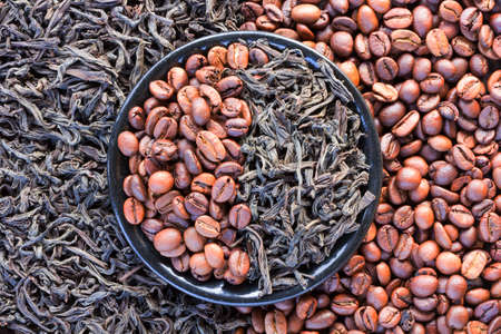 coffee beans and black tea leaves in a round saucer
