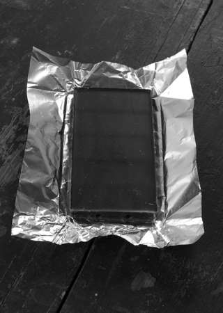 deployed: a bar of chocolate dark in foil deployed on an old black wooden desk close-up. black & white photo
