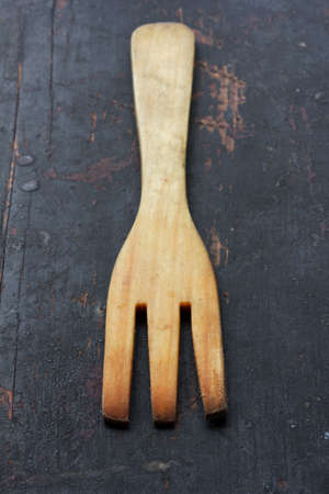 grunge cutlery: wooden kitchen fork, on the old black table closeup selective focus. rustic style. shallow depth of field