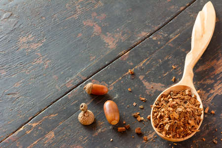 vegetative: acorns and crushed oak bark in a wooden spoon on an old black wooden table. vegetative raw materials for preparation of tea beverages, medicinal product. alternative medicine. Copy space. Free space for text. selective focus