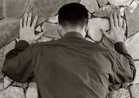 hoodlum: White man in a striped shirt stands with his back with his hands on the wall of stone. black white toning, shallow depth of field. the concept of police searches, arrest