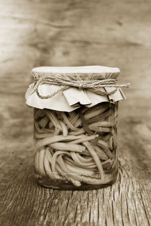 canning: pickled garlic sprouts in glass jar closeup. home canning. black and white photo