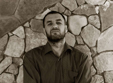 surly: portrait of grinning unshaven white man in a striped shirt against the wall of stone. black and white photo