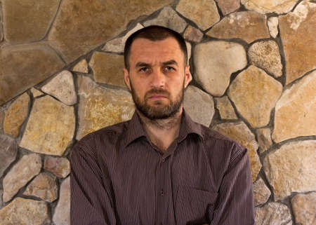 scowling: portrait of a sullen unshaven white man in a striped shirt against the wall of stone Stock Photo