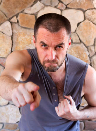 abhorrence: aggressive unshaven white man points his finger and tears on his shirt