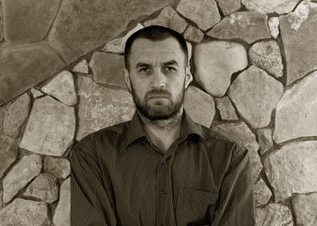 scowling: portrait of a sullen unshaven white man in a striped shirt against the wall of stone. black and white photo