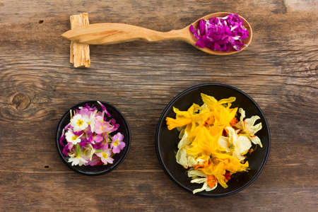 wooden aromatherapy: Fresh and dried flower petals in a wooden spoon on the old board. aromatherapy, herbal tea, homeopathic medicine.
