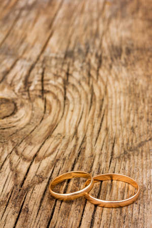 weddingrings: male and female wedding rings of gold on an old cracked wooden board. selective focus. Free space for text. Copy space Stock Photo