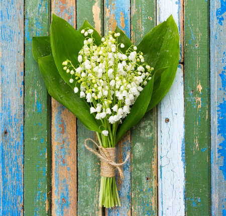 remnants: bouquet of lilies of the valley flowers with green leaves tied with twine in water droplets on wooden boards with remnants of old paint