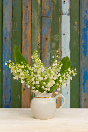 remnants: bouquet of lilies of the valley flowers with green leaves in a white jug on a background of wooden boards with remnants of old paint. with space for posting information