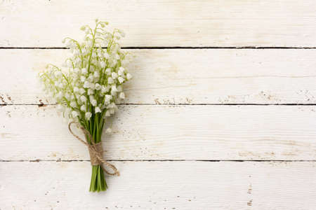 posting: lily of the valley bouquet of white flowers tied with string on a white background barn boards. with space for posting information