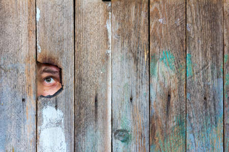 eavesdropper: the eyes of a man spying through a hole in an old wooden fence. with space for posting information