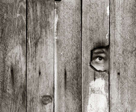 the eyes of a man spying through a hole in an old wooden fence. with space for posting information. black and white photo 写真素材