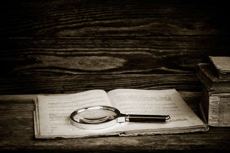poor eyesight: black and white photo. open old book with a magnifying glass and a stack of books on a wooden table. the concept of the study, the study. with space for text