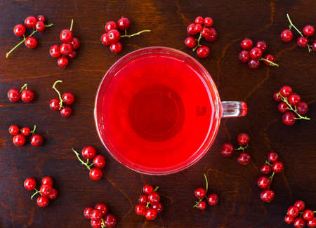 freshly squeezed red juice, and bunches of red currants on a brown wooden table with old paint. closeup flat lay