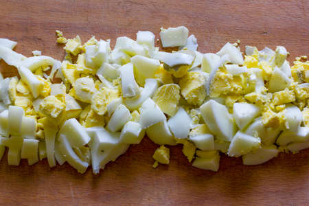 Finamente picado huevos duros en medio de una vieja tabla de cortar de madera close-up vista desde arriba
