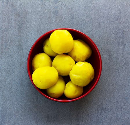 purified: purified boiled yellow potatoes in a red bowl on a gray background closeup, top view Stock Photo