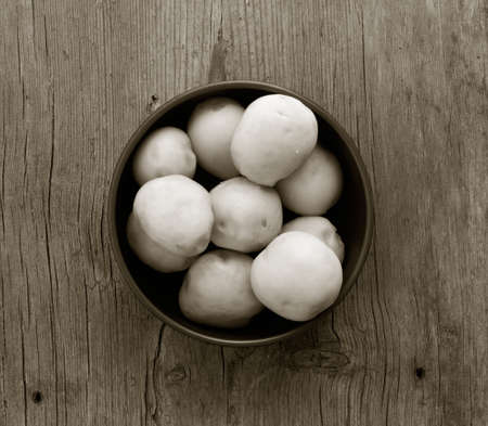 purified: purified boiled potatoes in a circular plate on an old wooden table with cracks closeup, top view. a monochrome image Stock Photo