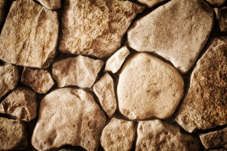 furred: background texture of a wall lined with natural stone close-up, toned photo