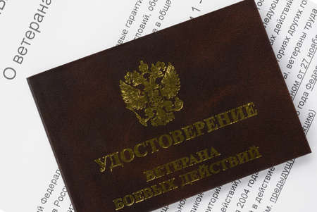 russian federation: veteran ID card on the background of the text of the federal law of the Russian Federation About veterans closeup Stock Photo