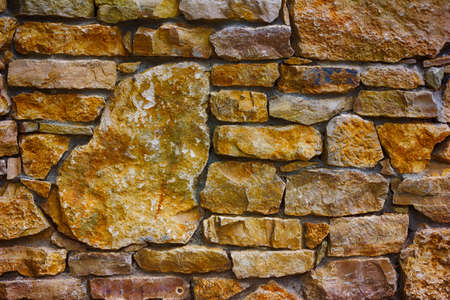 furred: texture background of a wall lined with natural stone close-up, toned photo