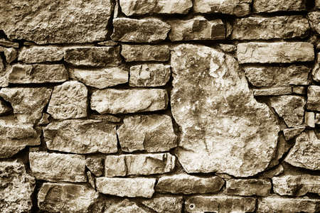 furred: black and white texture background of a wall lined with natural stone close-up, toned photo Stock Photo