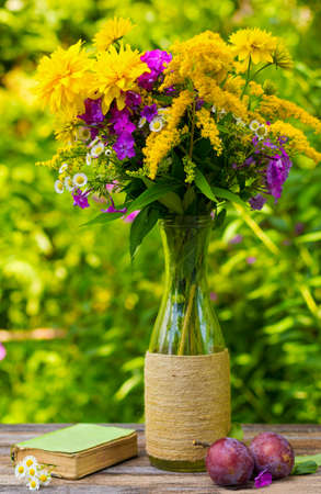 glass vase: a bouquet of flowers of goldenrod, phlox chrysanthemums in a glass vase, ripe plums and old book with daisies on the table on nature backgroun