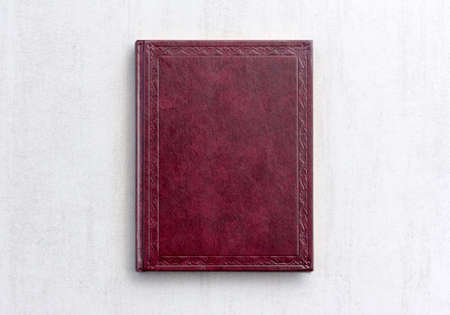 writ: book dark purple color on gray background close-up, top view