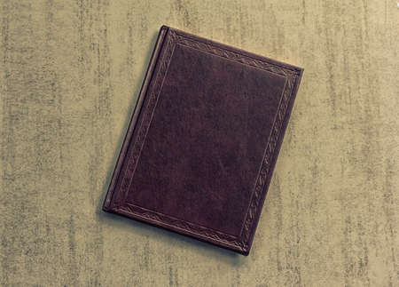 dark purple: the book is dark purple on a grey grunge background, top view. tinted photo, retro toned image Stock Photo