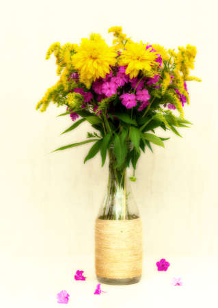 goldenrod: a bouquet of flowers of chrysanthemums, phlox and goldenrod in a glass bottle on a white background. toned photo Stock Photo