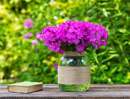 glass vase: bouquet of phlox flowers in a glass vase and an old book on the table on nature background, selective focus Stock Photo