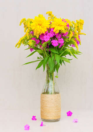 goldenrod: a bouquet of flowers of goldenrod, chrysanthemums, phlox in a glass vase on a gray background Stock Photo