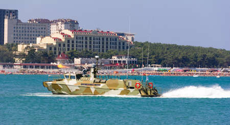 gunfire: military boat at full speed makes blank volley of guns on the city beach. Russia, Gelendzhik