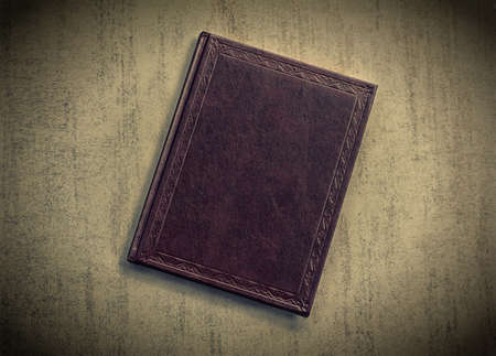 vignetting: the book is dark purple on a grey grunge background, top view. tinted photo with vignetting, retro toned image Stock Photo