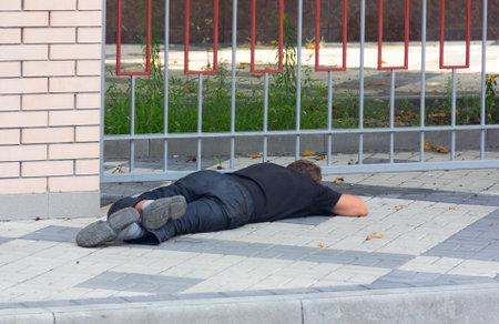 societal: KRASNODAR, RUSSIA - AUGUST 4, 2016: a Drunk homeless man lying on the sidewalk