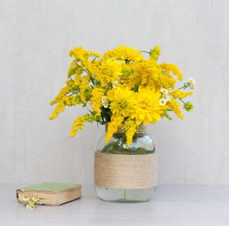 goldenrod: little old book, a bouquet of flowers chrysanthemums, goldenrod and daisies in a glass vase homemade closeup on gray background closeup Stock Photo