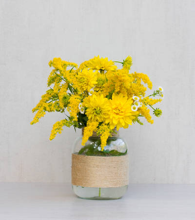 a bouquet of flowers of goldenrod and chrysanthemums in a glass vase homemade closeup on gray background closeup