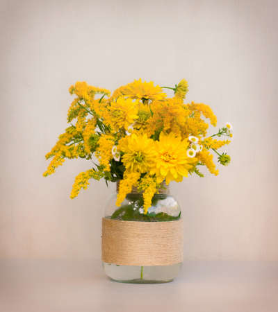 goldenrod: a bouquet of flowers of goldenrod and chrysanthemums in a glass vase homemade closeup on gray background closeup. tinted photo Stock Photo