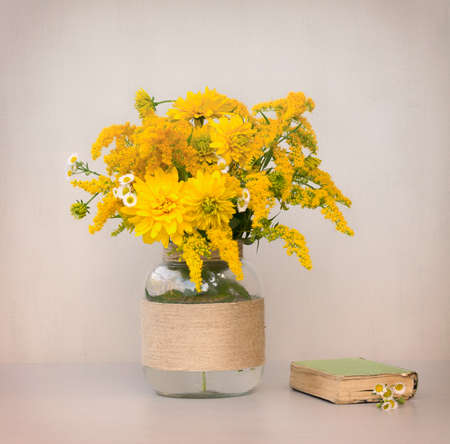 little old book, a bouquet of flowers chrysanthemums, goldenrod and daisies in a glass vase homemade closeup on gray background closeup. tinted photo Stock Photo