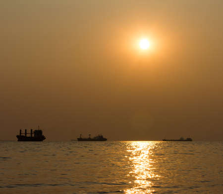 fishing fleet: Silhouettes of ships in the sea against the sunset. shallow depth of field Stock Photo