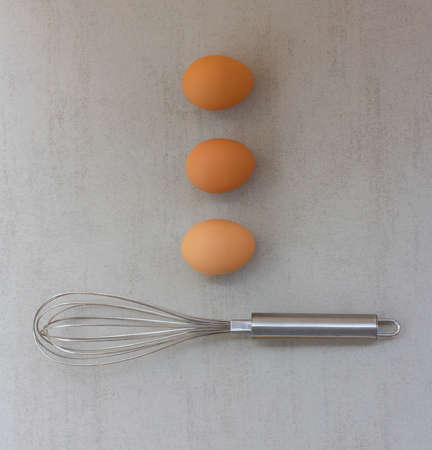 chicken egg are laid in a row and a steel crown on a gray background Stock Photo