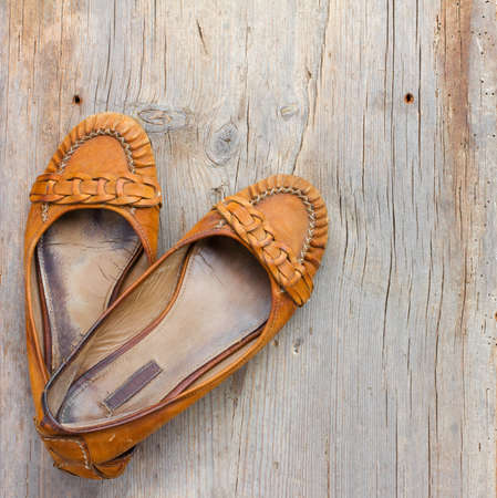 threadbare: old worn orange womens shoes made of genuine leather on old gray wooden board in the cracks, top view close-up Stock Photo